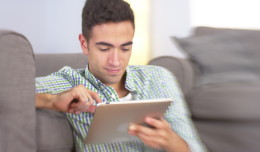 stock-footage-hispanic-man-using-tablet-on-floor